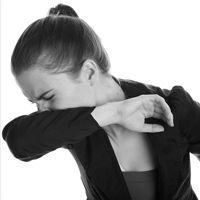 Woman coughing or sneezing in her sleeve