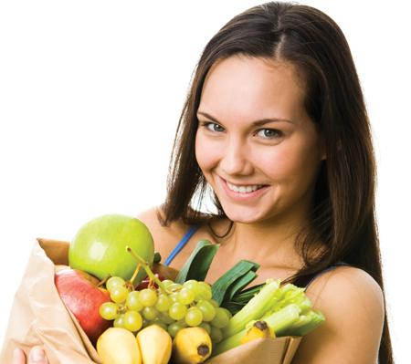 Girl with grocery bag full of fruits and vegetables