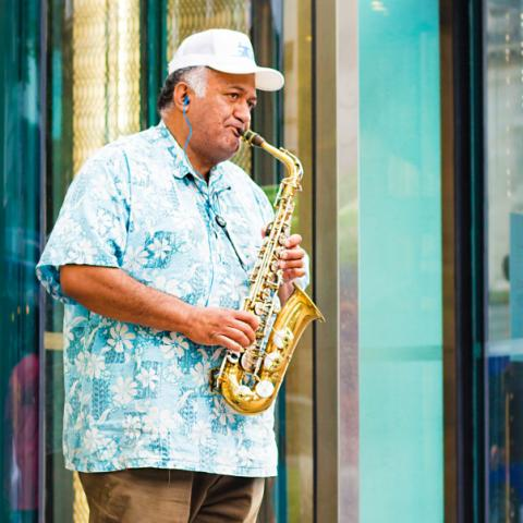 Man with cap playing saxophone