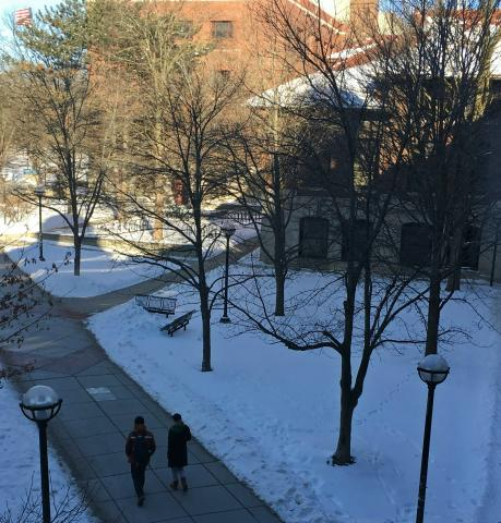 two people walk on campus in winter