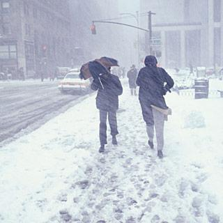 Two people walking down a street through snow