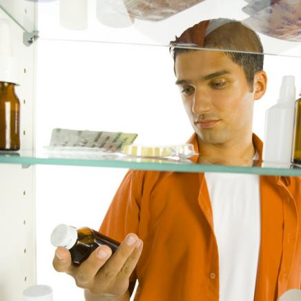 Man looking at items from a medicine cabinet