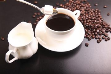 Coffee cup filled with coffee. Cream and sugar. Coffee beans in the background.