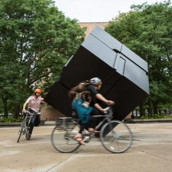 People riding bikes around the Cube at University of Michigan