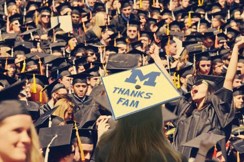 "UM commencement female student in the foreground with cap decorated to say ""Thanks Fam"""