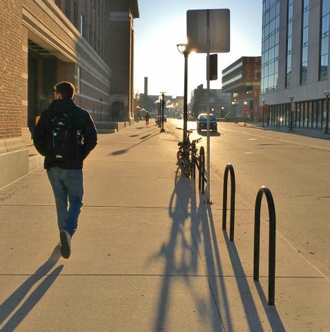 student walking at sunrise