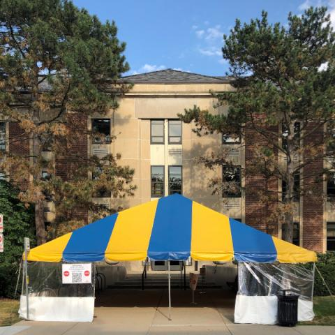 Yellow and blue striped tent in front of University Health Service