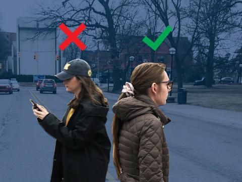 Two women crossing a street. One looks at her phone the other does not.