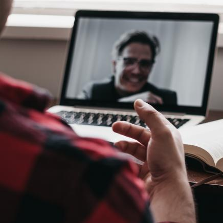 Photo by Dylan Ferreira from Unsplash - Person talking to another person over Zoom