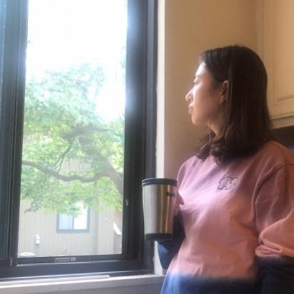 Student looking out a window of Northwood apartment