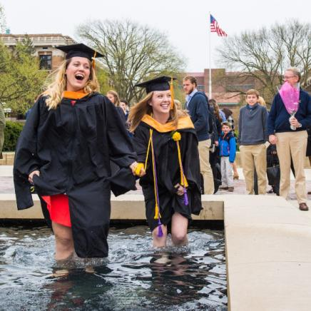two graduating students walk through fountain