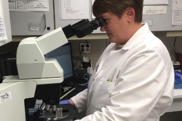 Women in lab coat looking into a microscope