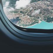 view from airplane window with turquoise lake below, Photo by Maria Butyrina on Unsplash