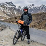 man straddling bicycle on mountain road, Photo by Mohit Tomar on Unsplash